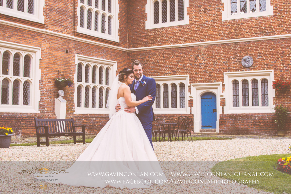 romantic portrait of the bride and groom in the inner courtyard of Gosfield Hall.Wedding photography at Gosfield Hall by Essex wedding photographer gavin conlan photography Ltd