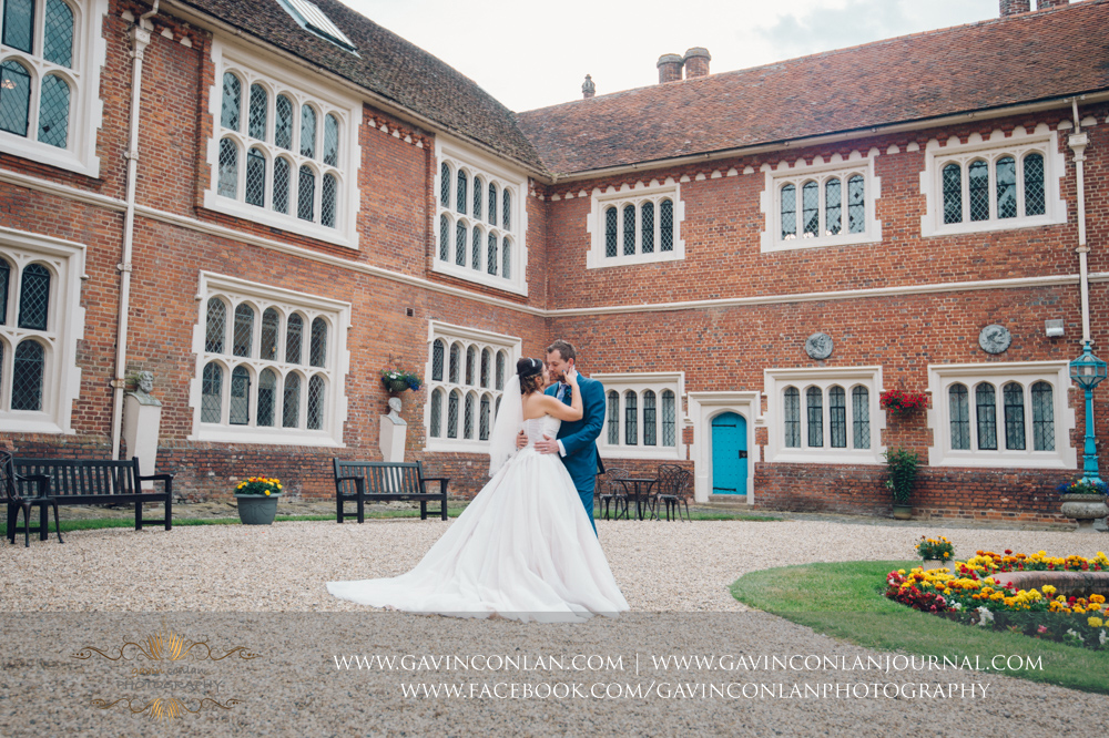 creative portrait of the bride and groom sharing a kiss in the inner courtyard of Gosfield Hall.Wedding photography at Gosfield Hall by Essex wedding photographer gavin conlan photography Ltd