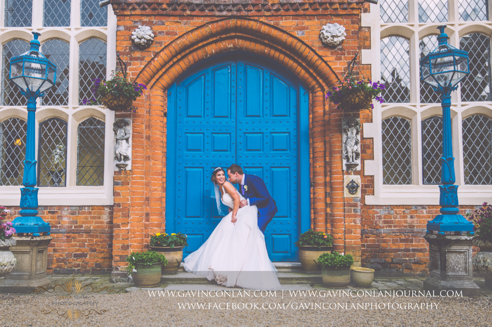 fun and sexy portrait of the bride and groom having fun in front of the blue doors in the inner courtyard of Gosfield Hall.Wedding photography at Gosfield Hall by Essex wedding photographer gavin conlan photography Ltd