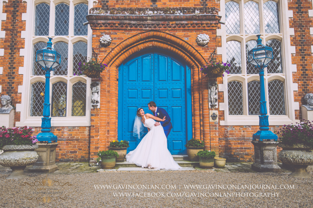 sexy portrait of the bride and groom having fun in front of the blue doors in the inner courtyard of Gosfield Hall.Wedding photography at Gosfield Hall by Essex wedding photographer gavin conlan photography Ltd