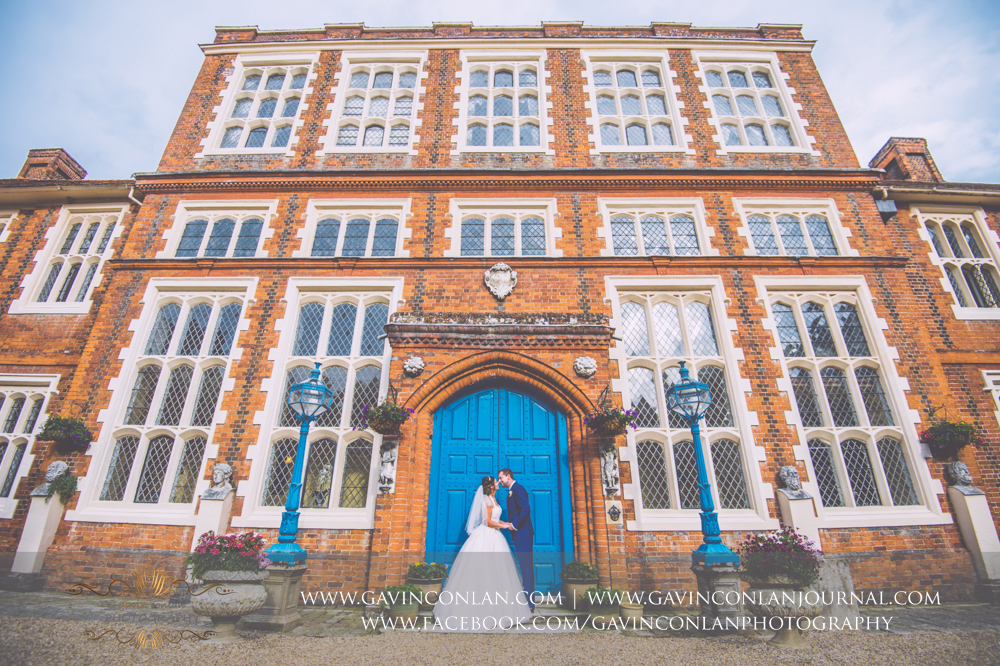 classic portrait of the bride and groom posing in front of the blue doors in the inner courtyard of Gosfield Hall.Wedding photography at Gosfield Hall by Essex wedding photographer gavin conlan photography Ltd