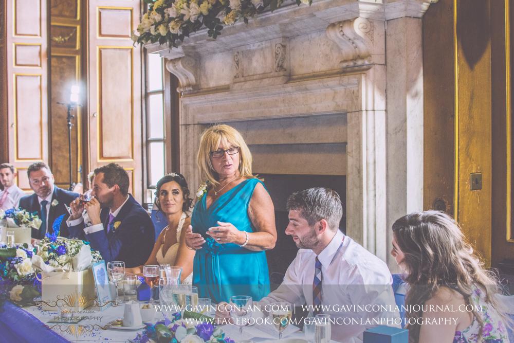 portrait of the brides mother during her wedding breakfast speech in the ballroom.Wedding photography at Gosfield Hall by Essex wedding photographer gavin conlan photography Ltd