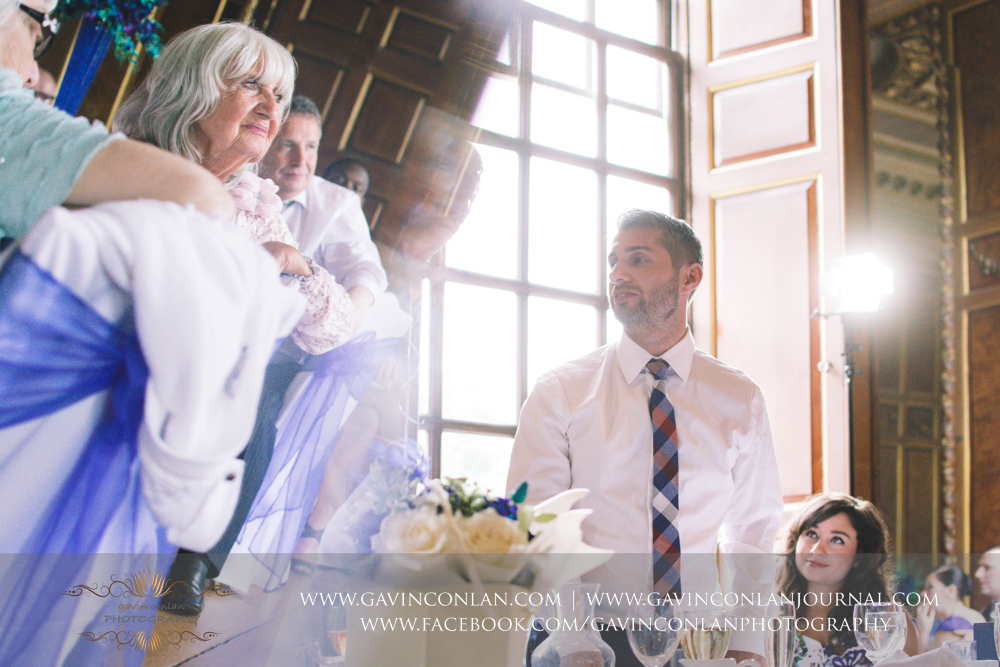 creative portrait of the bride's brother during hiswedding breakfast speech with the brides grandmother appearing in the reflection, a single frame no photoshop.Wedding photography at Gosfield Hall by Essex wedding photographer gavin conlan photography Ltd