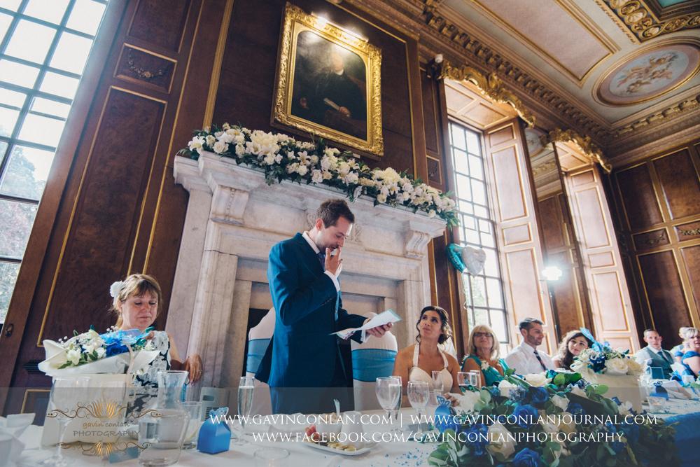 portrait of the groom reading apoem during hiswedding breakfast speech in the ballroom.Wedding photography at Gosfield Hall by Essex wedding photographer gavin conlan photography Ltd