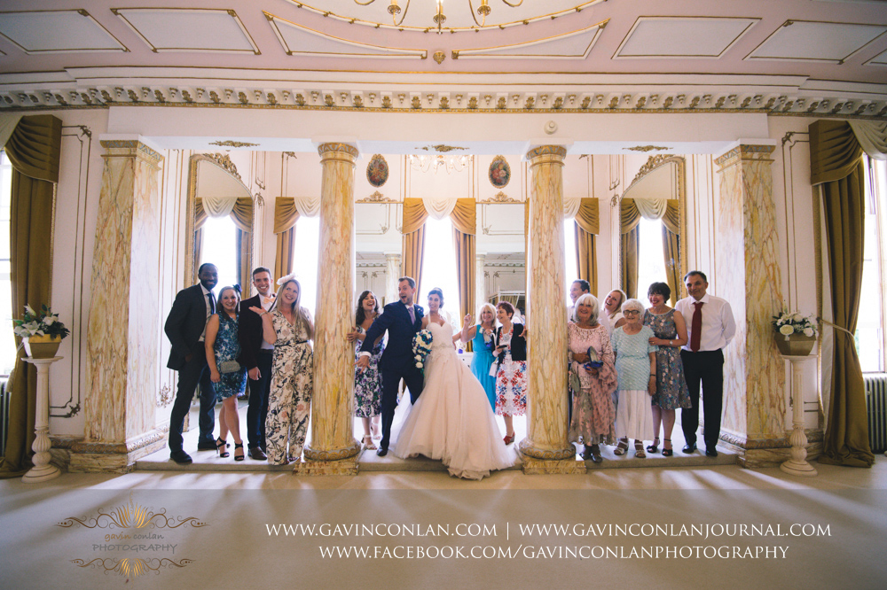 fun portrait of the bride and groom with some of their guest in The Rococco Suite during their tour of the stunning rooms.Wedding photography at Gosfield Hall by Essex wedding photographer gavin conlan photography Ltd