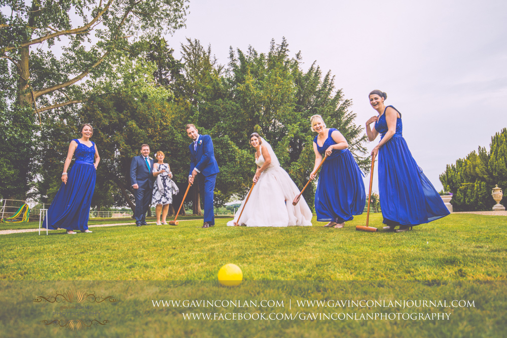 fun portrait of the bride, groom and the bridesmaids playingcroquet on the lawn outside the main entrance of Gosfield Hall with the grooms mother and step dad looking on in the background.Wedding photography at Gosfield Hall by Essex wedding photographer gavin conlan photography Ltd