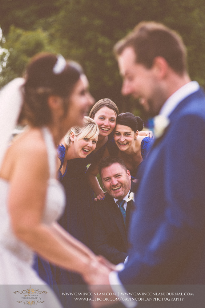 funand creative portrait of the bridesmaids and best man looking at the camera with the bride and groom in the foreground.Wedding photography at Gosfield Hall by Essex wedding photographer gavin conlan photography Ltd
