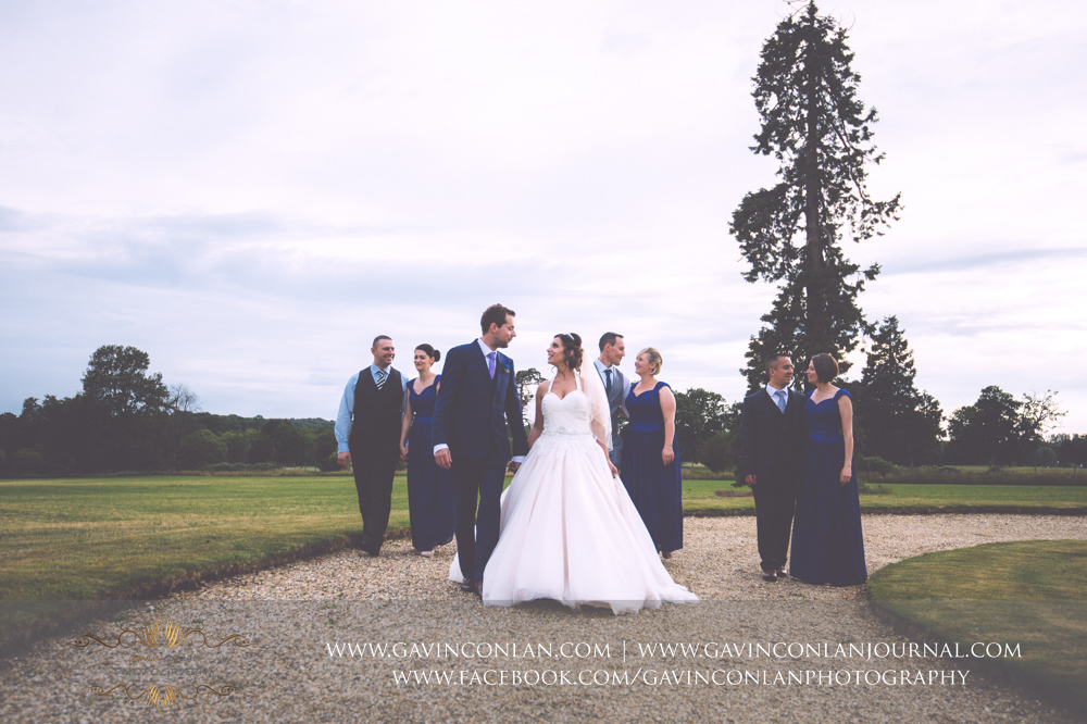 creative fashion portrait of the bride, groom, bridesmaids and their partners posing walking past the fountain in the grounds of Gosfield Hall.Wedding photography at Gosfield Hall by Essex wedding photographer gavin conlan photography Ltd