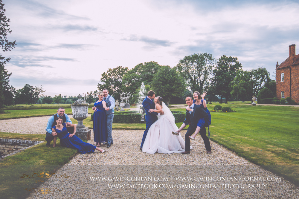 creative and fun portrait of the bride, groom, bridesmaids and their partners posing in front of the fountain in the grounds of Gosfield Hall.Wedding photography at Gosfield Hall by Essex wedding photographer gavin conlan photography Ltd