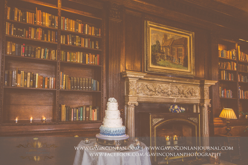creative detail photograph of the wedding cake in the library with candles lit ready for the official cake cutting.Wedding photography at Gosfield Hall by Essex wedding photographer gavin conlan photography Ltd