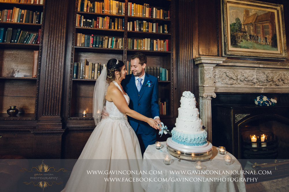 beautiful portrait of the bride and groom cutting their wedding cake in the library.Wedding photography at Gosfield Hall by Essex wedding photographer gavin conlan photography Ltd