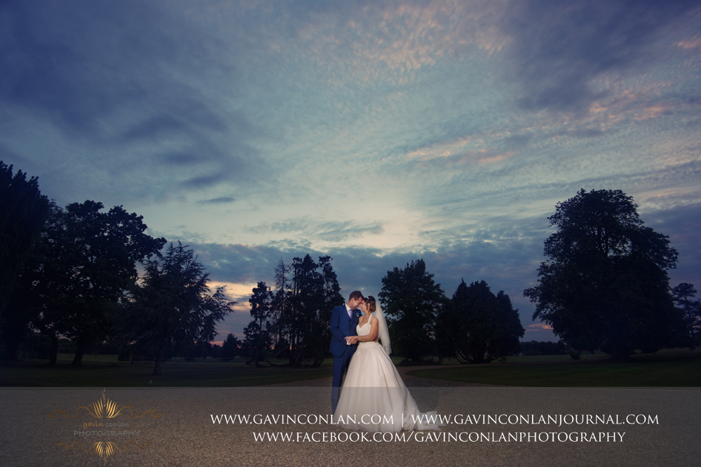 creative night time portrait of the bride and groom in the grounds of Gosfield Hall. Wedding photography at Gosfield Hall by Essex wedding photographer gavin conlan photography Ltd