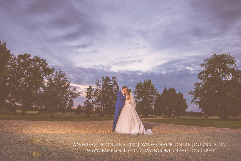 creative night time portrait of the bride and groom sharing a kiss in the grounds of Gosfield Hall.Wedding photography at Gosfield Hall by Essex wedding photographer gavin conlan photography Ltd