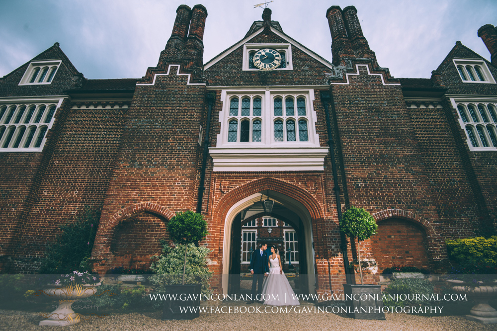 creative portrait of the bride and groom posing in the archway under the clock tower in the grounds of Gosfield Hall.Wedding photography at Gosfield Hall by Essex wedding photographer gavin conlan photography Ltd