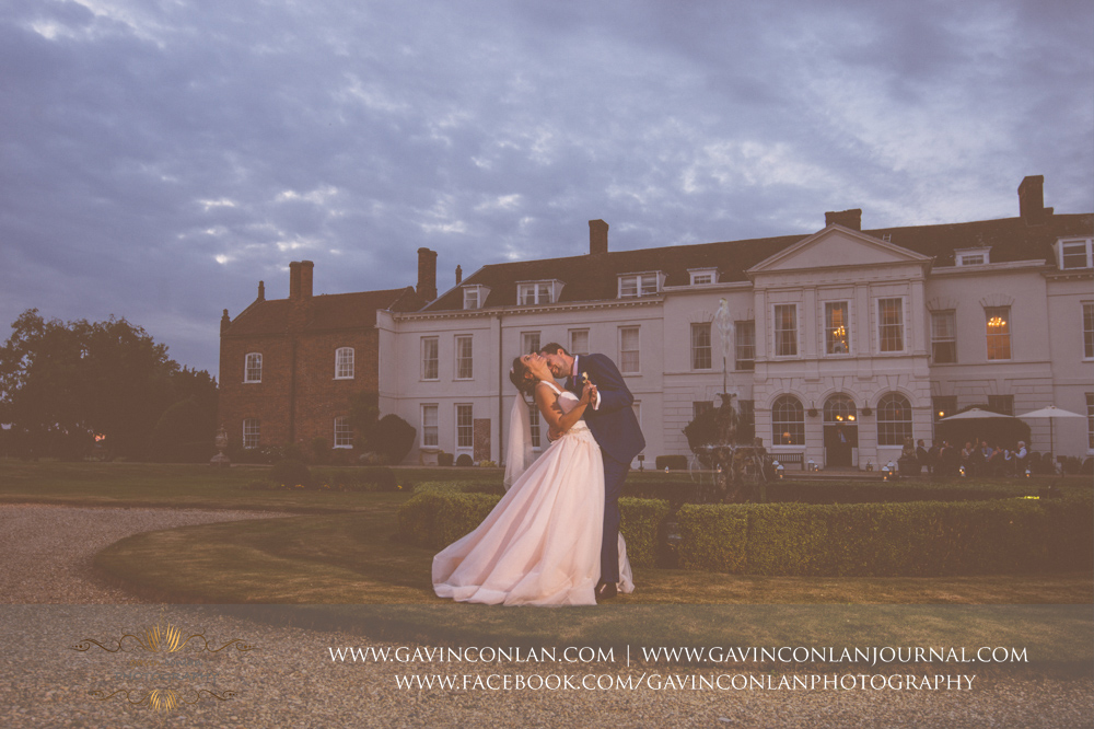 beautiful and romantic portrait of the groom kissing his bride on the neck in front of the fountain in the grounds of Gosfield Hall.Wedding photography at Gosfield Hall by Essex wedding photographer gavin conlan photography Ltd