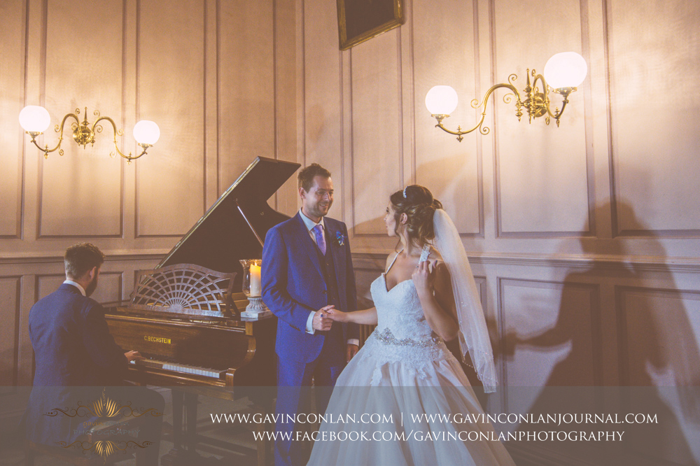 creative and romantic portrait of the bride and groom sharing a moment and the piano is being played.Wedding photography at Gosfield Hall by Essex wedding photographer gavin conlan photography Ltd