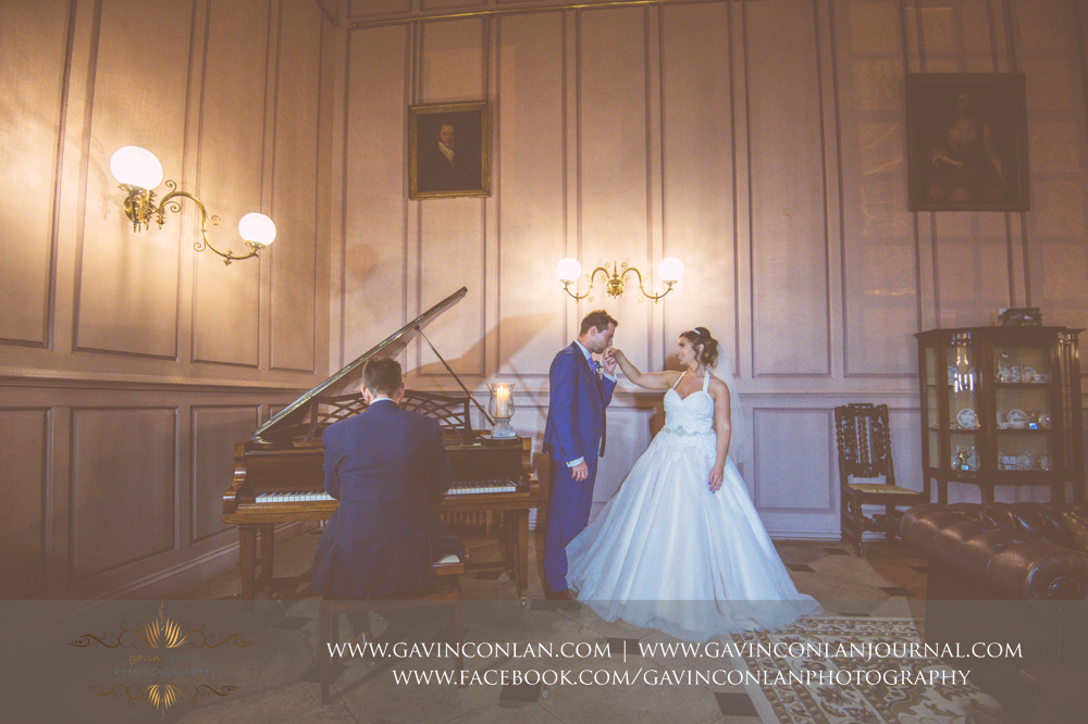 creative and romantic portrait of the groom kissing hisbrides hand as the piano is being played.Wedding photography at Gosfield Hall by Essex wedding photographer gavin conlan photography Ltd