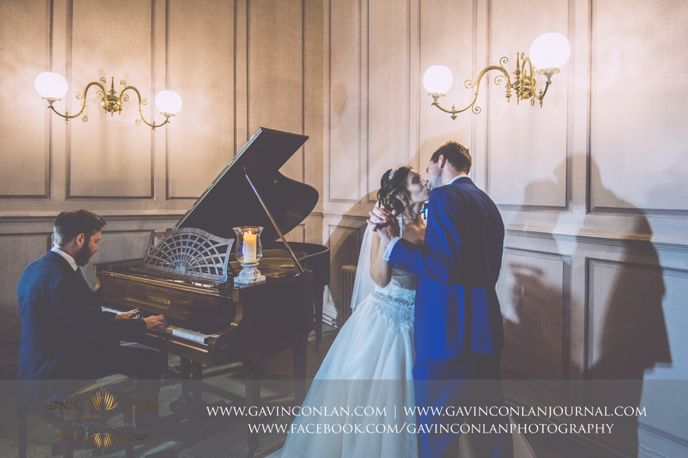 creative and romantic portrait of the bride and groom sharing a kiss next to the piano as its being played.Wedding photography at Gosfield Hall by Essex wedding photographer gavin conlan photography Ltd