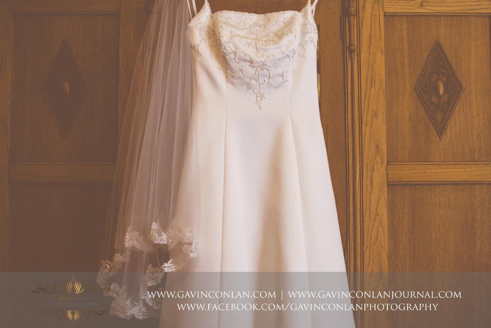 creative close up detail photograph of the brides wedding dress on display in the luxurious Balcony Suite. Wedding photography at  Alconbury Guest House  by  gavin conlan photography Ltd