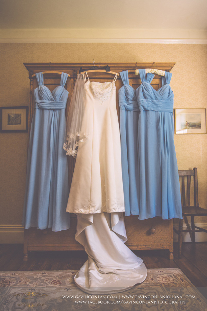creative detail photograph of the brides wedding dress and three bridesmaids dresses on display in the luxurious Balcony Suite. Wedding photography at  Alconbury Guest House  by  gavin conlan photography Ltd