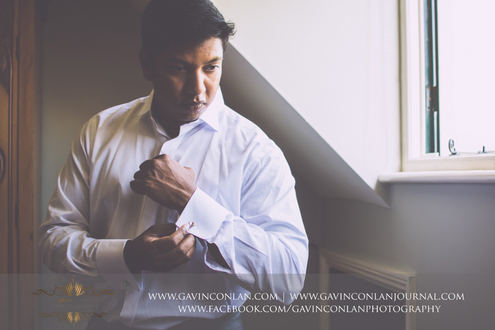 creative fashion portrait of the groom putting on his cuff links. Wedding photography at  Alconbury Guest House  by  gavin conlan photography Ltd