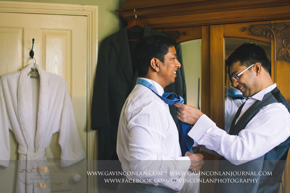 creative portrait of the best man helping the groom get dressed. Wedding photography at  Alconbury Guest House  by  gavin conlan photography Ltd