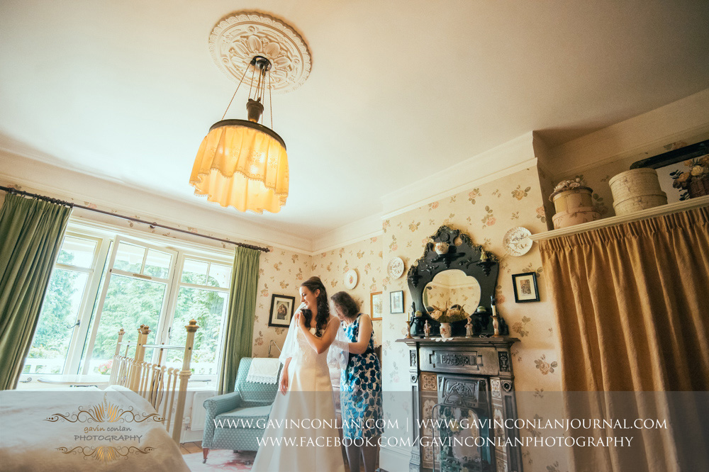 creative bridal portrait of the mother of the bride helping her daughter get dressed in the luxurious Balcony Suite. Wedding photography at  Alconbury Guest House  by  gavin conlan photography Ltd