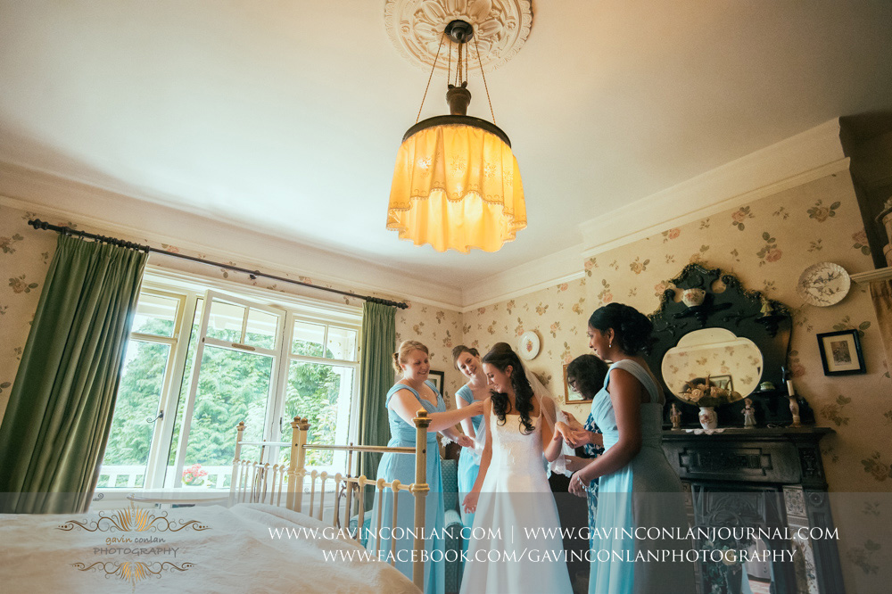 creative bridal portrait of the mother of the bride and the bridesmaids helping the bride get dressed in the luxurious Balcony Suite. Wedding photography at  Alconbury Guest House  by  gavin conlan photography Ltd