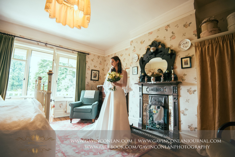creative bridal portrait holding her bouquet of flowers in the luxurious Balcony Suite. Wedding photography at  Alconbury Guest House  by  gavin conlan photography Ltd