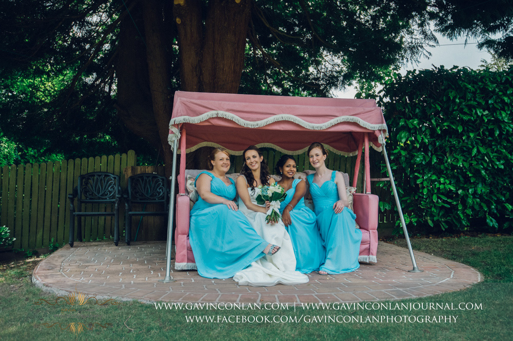 creative portrait of the bride and her bridesmaids sitting on the pink garden swing chair in the garden of the Alconbury Guest House. Wedding photography at  Alconbury Guest House  by  gavin conlan photography Ltd