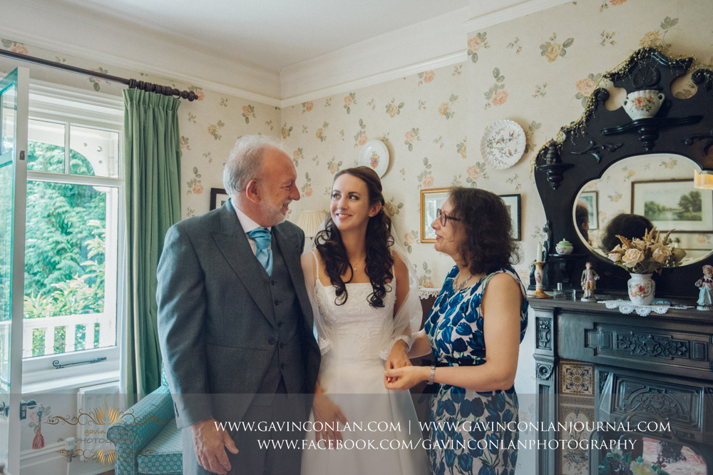 creative portrait of the bride with her mother and father in the luxurious Balcony Suite. Wedding photography at  Alconbury Guest House  by  gavin conlan photography Ltd