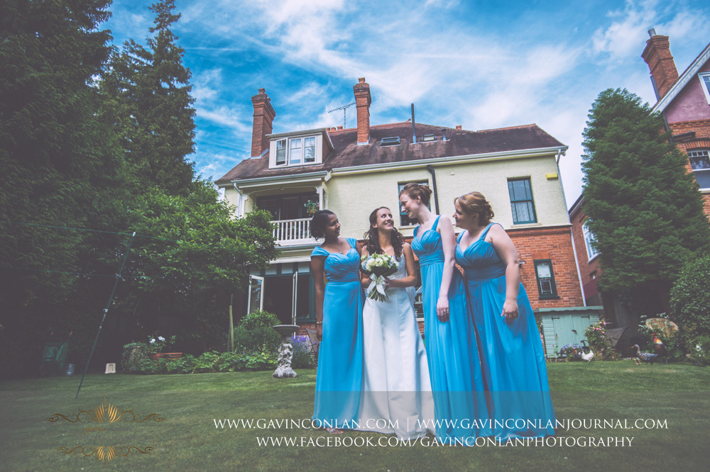 creative portrait of the bride and her bridesmaids laughing together in the garden of Alconbury Guest House. Wedding photography at  Alconbury Guest House  by  gavin conlan photography Ltd