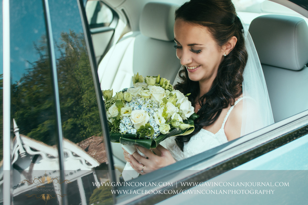creative portrait of the bride looking at her flowers whilst sitting in her wedding car. Wedding photography at  High Rocks  by preferred supplier  gavin conlan photography Ltd