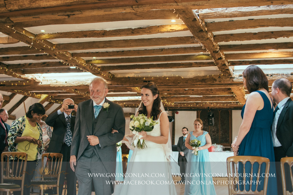 creative ceremony portrait of the bride and her father walking down the aisle smiling towards the groom in the Presidents Suite of High Rocks. Wedding photography at  High Rocks  by preferred supplier  gavin conlan photography Ltd