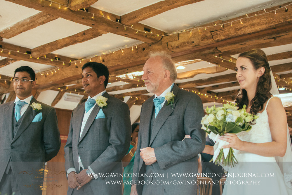 creative ceremony portrait of the bride, brides father, groom and best man waiting for the ceremony to begin in Presidents Suite of High Rocks. Wedding photography at  High Rocks  by preferred supplier  gavin conlan photography Ltd