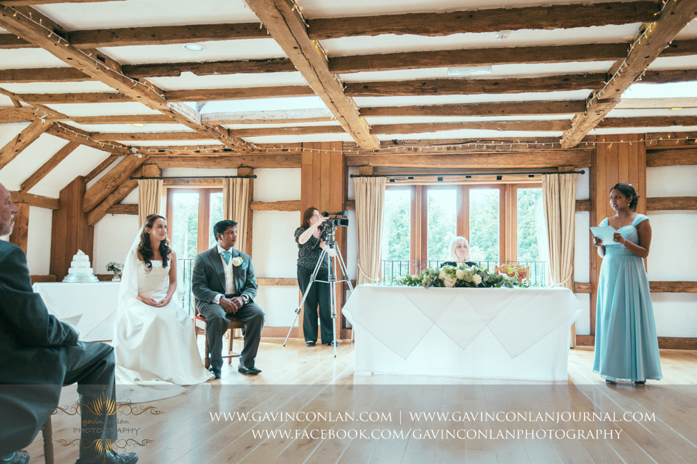 creative ceremony portrait of the bride and groom sitting down listening to one of the bridesmaids doing her reading in the Presidents Suite of High Rocks. Wedding photography at  High Rocks  by preferred supplier  gavin conlan photography Ltd