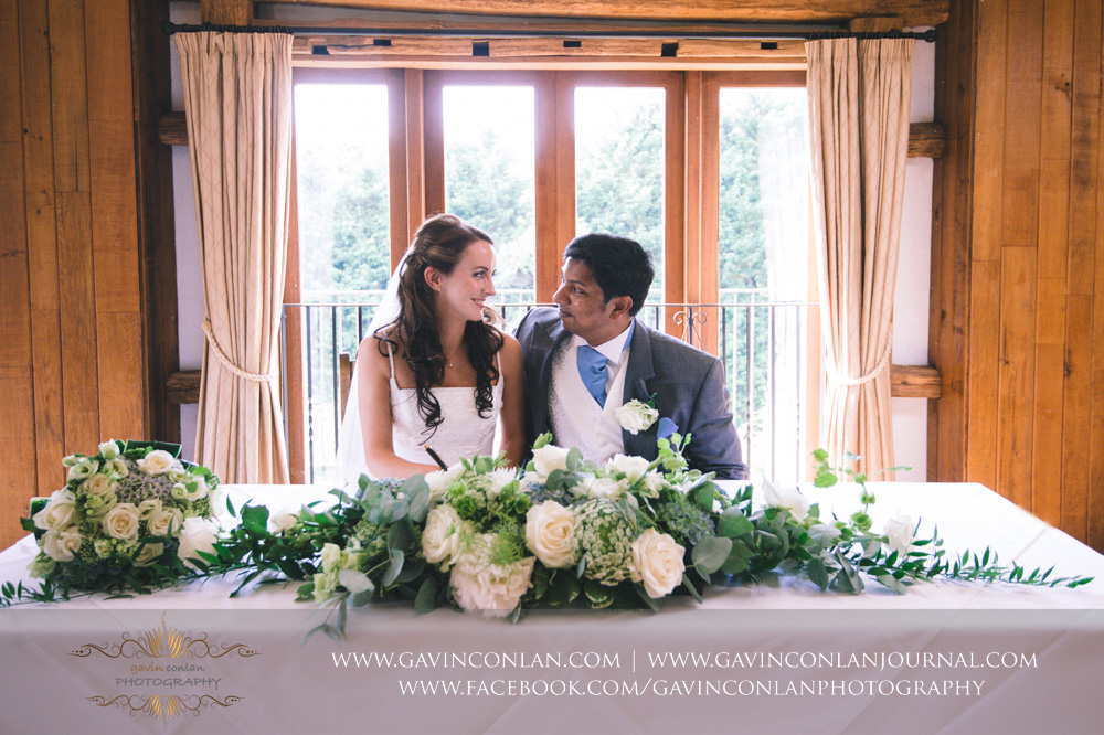 creative portrait of the bride and groom looking at each other after signing the registrar in the Presidents Suite of High Rocks. Wedding photography at  High Rocks  by preferred supplier  gavin conlan photography Ltd
