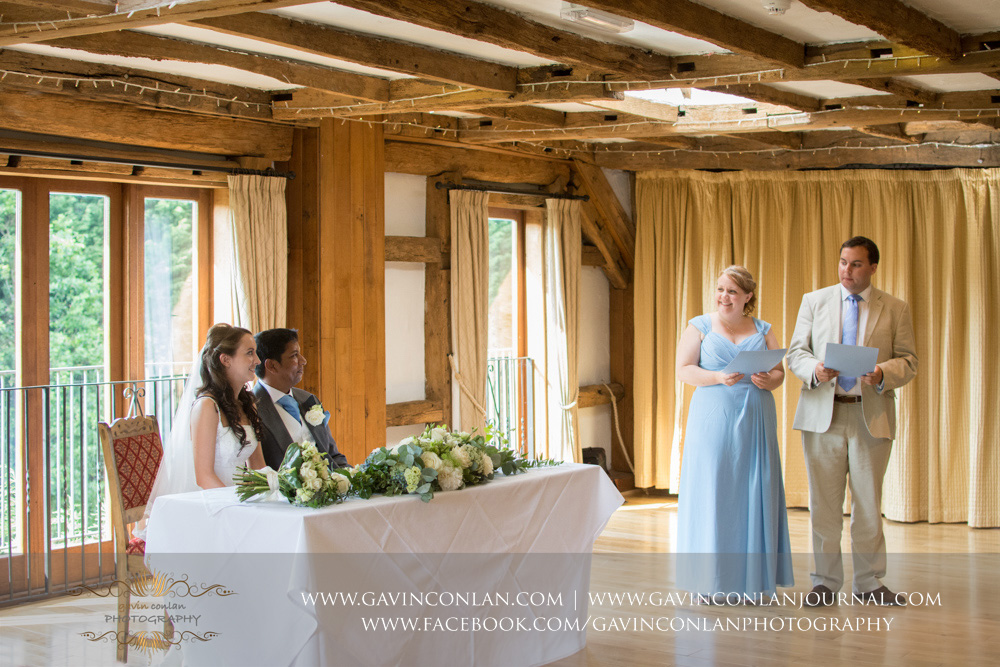 creative ceremony portrait of the bride and groom sitting down listening to one of the bridesmaids and guest giving their reading in the Presidents Suite of High Rocks.Wedding photography at  High Rocks  by preferred supplier  gavin conlan photography Ltd