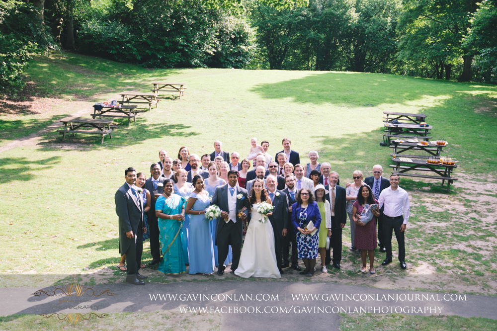creative portrait of the bride and groom with all their guests during their drinks reception in The Rocks. Wedding photography at  High Rocks  by preferred supplier  gavin conlan photography Ltd