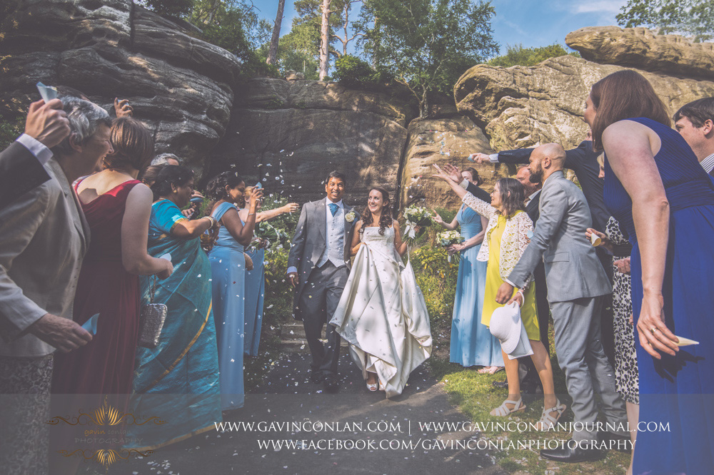 creative portrait of the guests throwing confetti over the bride and groom in The Rocks. Wedding photography at  High Rocks  by preferred supplier  gavin conlan photography Ltd