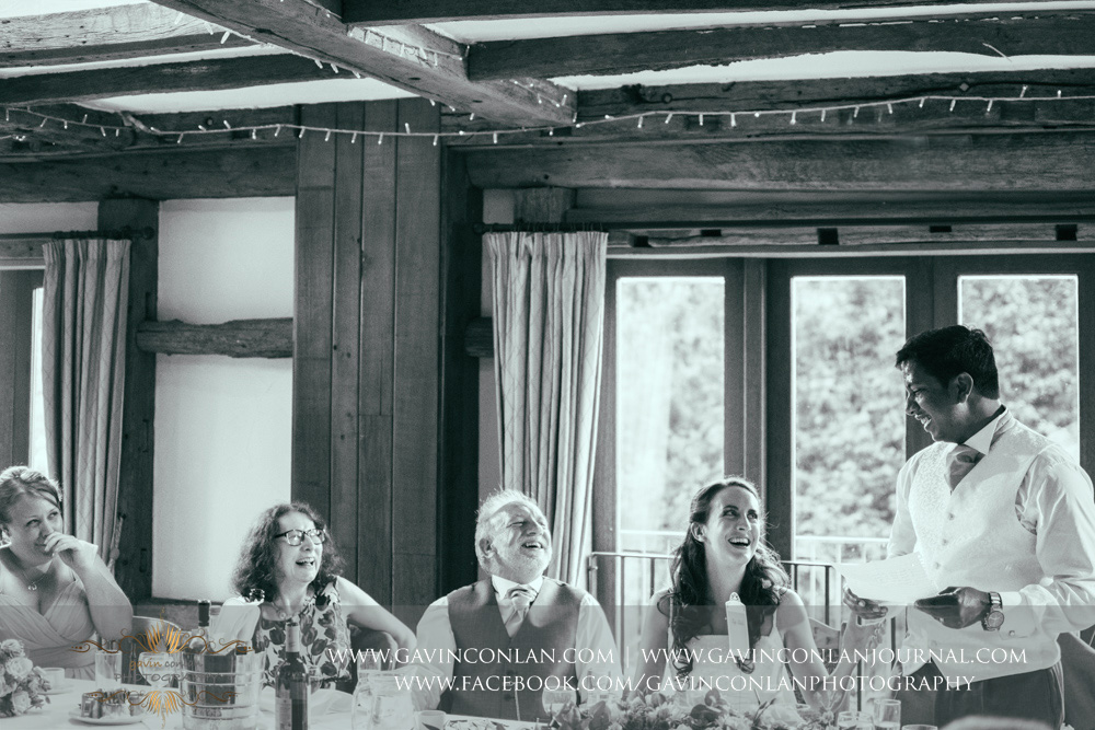 creative black and white portrait of the groom during his speech in the Presidents Suite of High Rocks. Wedding photography at  High Rocks  by preferred supplier  gavin conlan photography Ltd