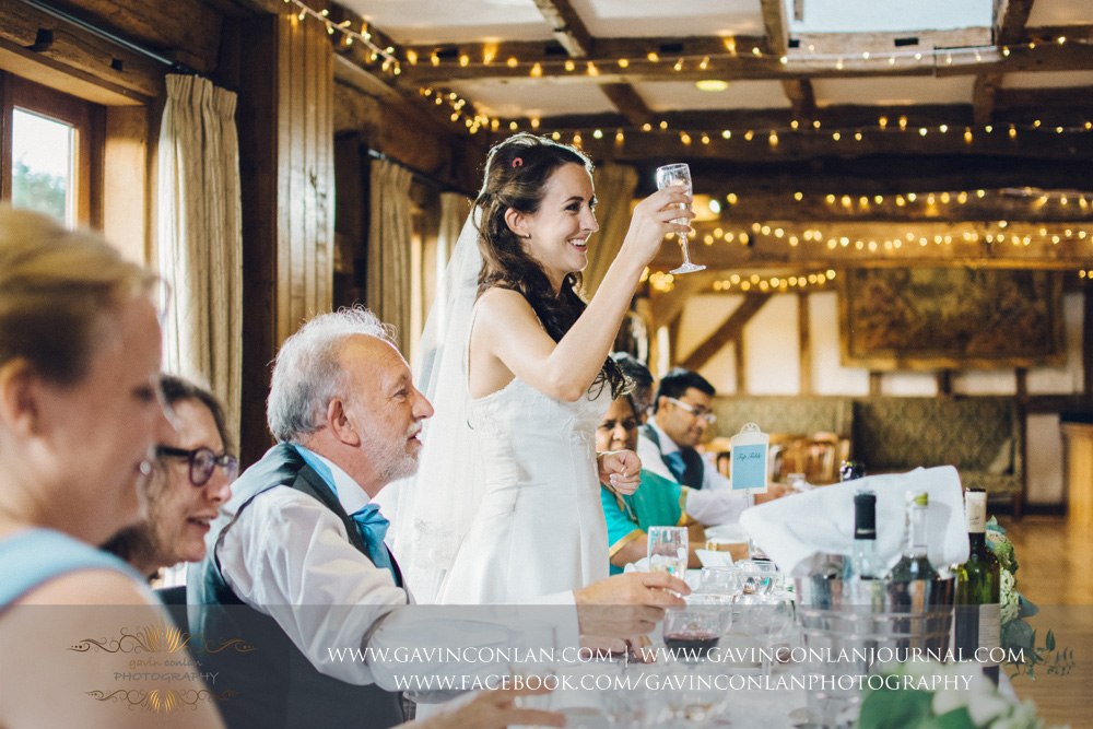 creative portrait of the bride giving a toast to absent family and friends during her speech in the Presidents Suite of High Rocks. Wedding photography at  High Rocks  by preferred supplier  gavin conlan photography Ltd