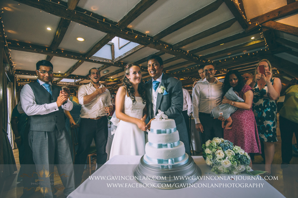 creative portrait of the bride and groom cutting their wedding cake with all their guests looking on in celebration. Wedding photography at  High Rocks  by preferred supplier  gavin conlan photography Ltd