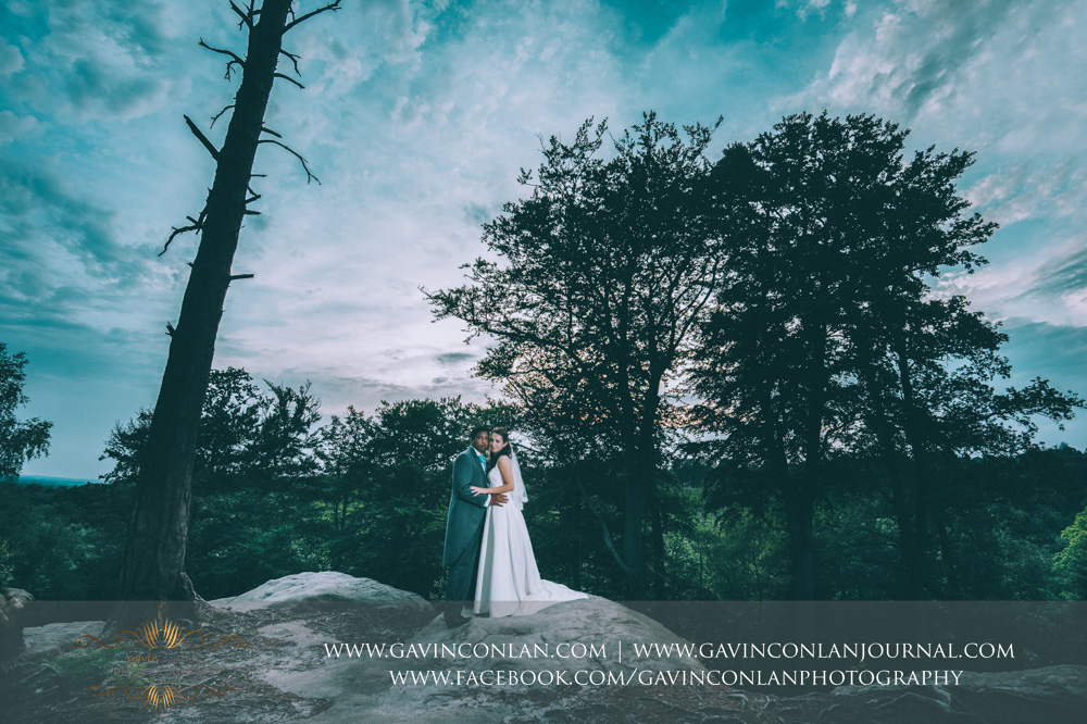 creative portrait of the bride and groom cuddling and looking at the camera in The Rocks. Wedding photography at  High Rocks  by preferred supplier  gavin conlan photography Ltd