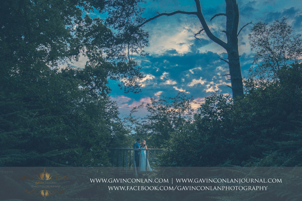 creative fine art portrait of the bride and groom posing on a bridge in the grounds of the Rocks. Wedding photography at  High Rocks  by preferred supplier  gavin conlan photography Ltd