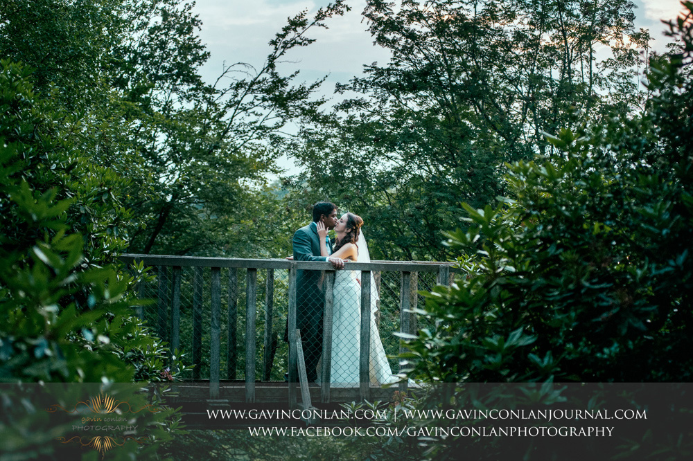 creative portrait of the bride and groom kissing on a bridge in the grounds of the Rocks. Wedding photography at  High Rocks  by preferred supplier  gavin conlan photography Ltd