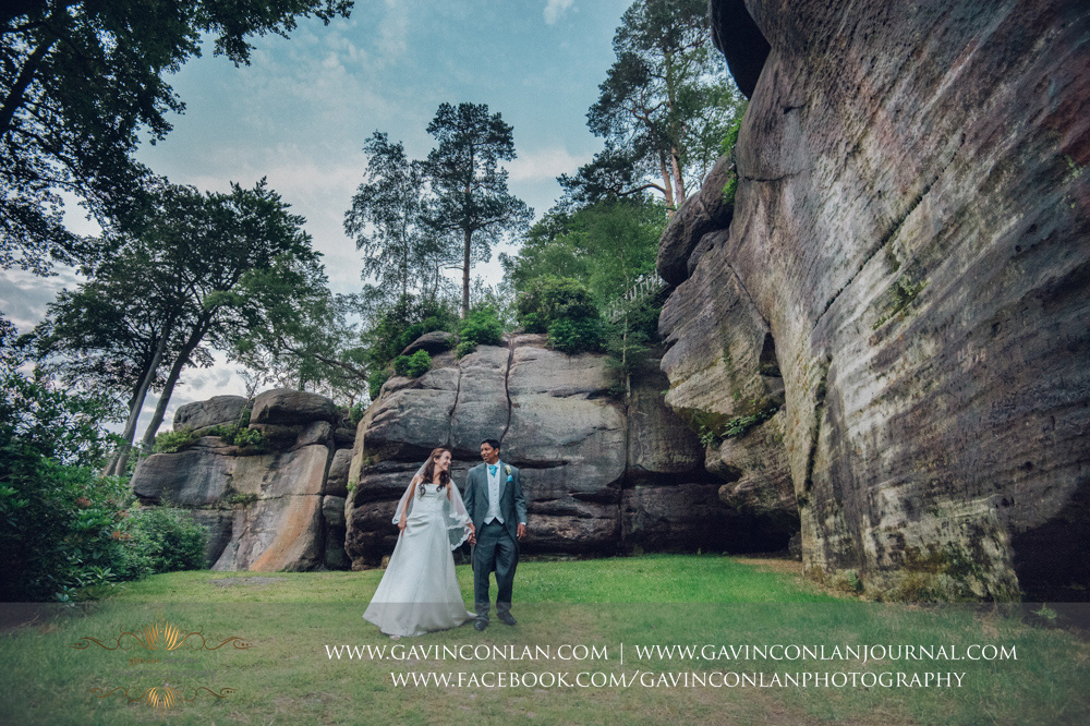 fun and creative portrait of the bride and groom walking along laughing in the grounds of the Rocks. Wedding photography at  High Rocks  by preferred supplier  gavin conlan photography Ltd