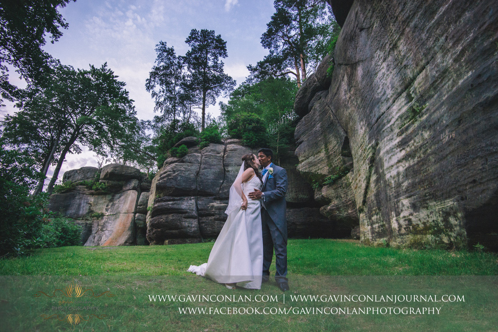 fun and romantic portrait of the bride and groom kissing in the grounds of the Rocks. Wedding photography at  High Rocks  by preferred supplier  gavin conlan photography Ltd