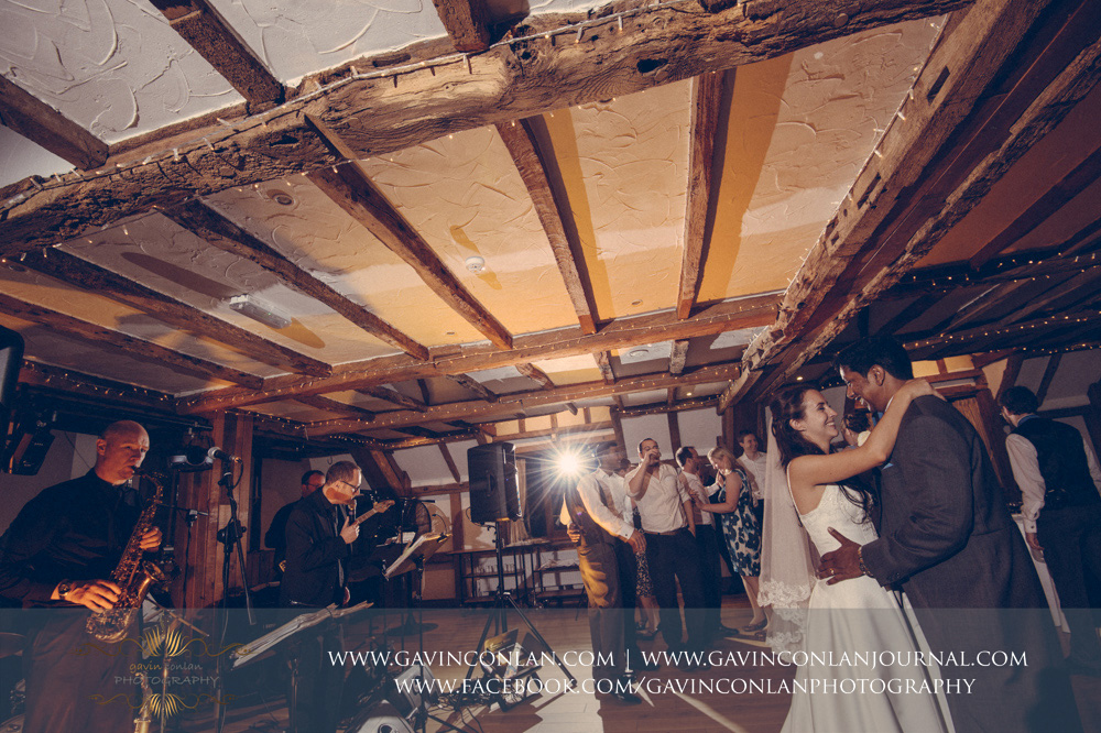 creative portrait of the bride and groom and the band playing during their first dance in the Presidents Suite of High Rocks. Wedding photography at  High Rocks  by preferred supplier  gavin conlan photography Ltd