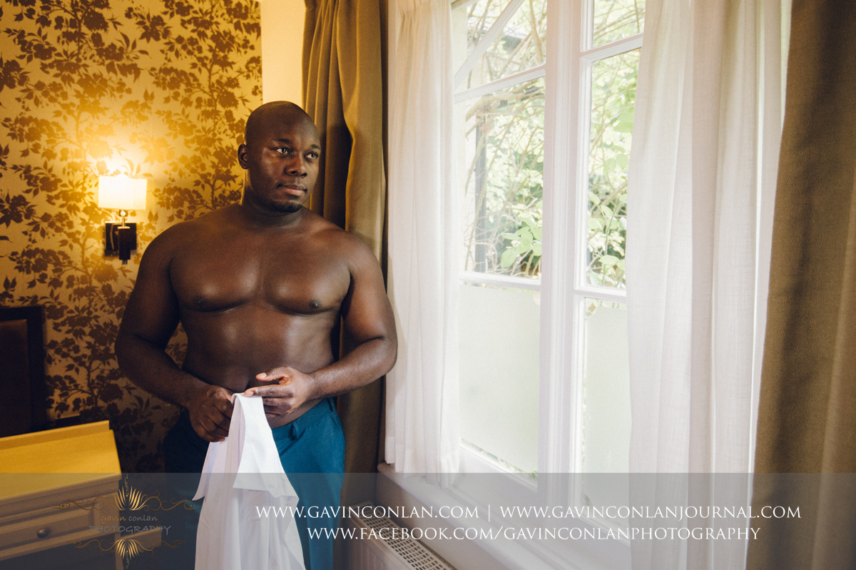 creative portrait of the groom holding his shirt in his hands at the Best Western Ivy Hill Hotel. Wedding photography at  Best Western Ivy Hill Hotel  by  gavin conlan photography Ltd